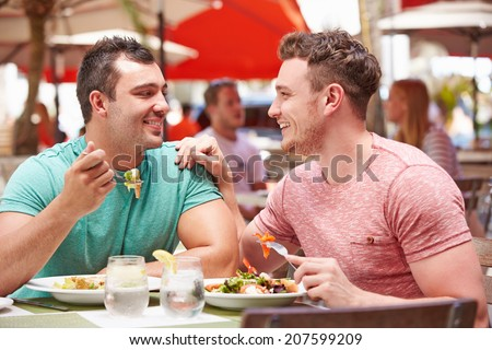 Male Couple Enjoying Lunch In Outdoor Restaurant - stock photo