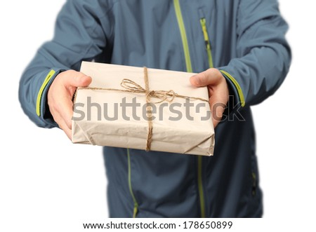 Male courier service worker or postman holding parcel delivering package - stock photo