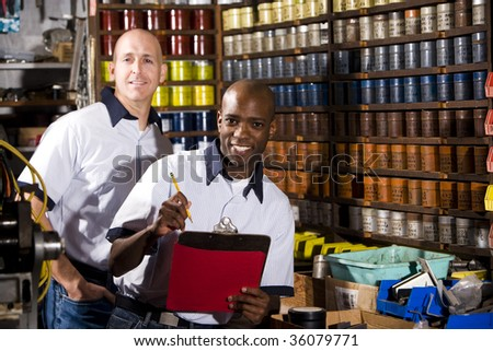 Male coworkers working in front of colored inks in print shop - stock photo