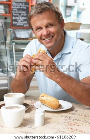 Male Customer Enjoying Sandwich And Coffee In Cafe - stock photo