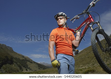 Male cyclist carrying bike against hills and blue sky - stock photo