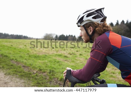Male cyclist leaning on bike in open countryside, close up - stock photo