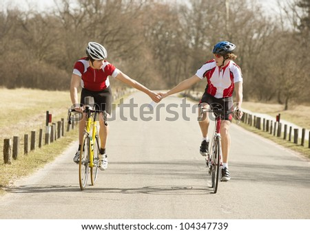 Male cyclist passing water bottle to other athlete while riding bicycles on road - stock photo