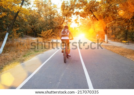 Male cyclist riding a bike on an open road on a sunny day - stock photo
