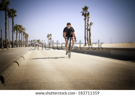 Male cyclist riding a road bike on the beach walkway in Santa Monica - stock photo