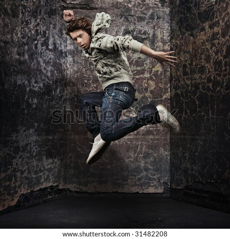 Male dancer posing over grunge wall - stock photo