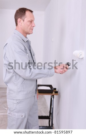 Male decorating painting a room white - stock photo