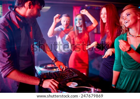 Male deejay adjusting sound with group of cute girls dancing near by - stock photo