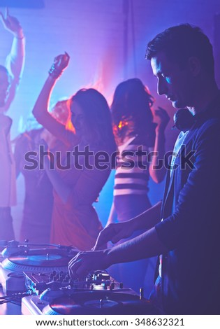 Male deejay mixing sounds on background of dancing girls - stock photo