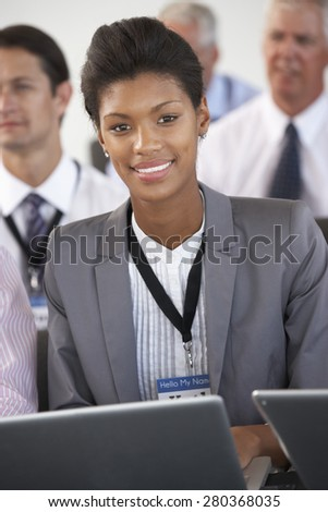 Male Delegate Listening To Presentation At Conference making Notes On Digital Tablet - stock photo