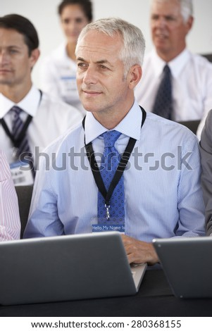 Male Delegate Listening To Presentation At Conference Making Notes On Laptop - stock photo