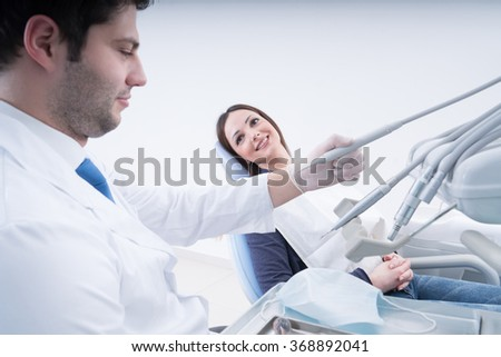 Male dentist, and female patient in dental practice - stock photo