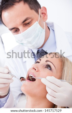 Male Dentist Examining Female Patient In Clinic - stock photo