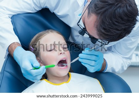Male dentist examining girls teeth in the dentists chair - stock photo