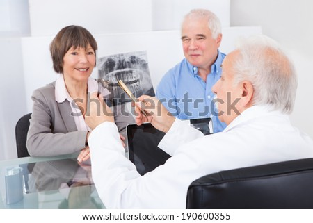 Male dentist explaining dental x-ray to senior couple in clinic - stock photo