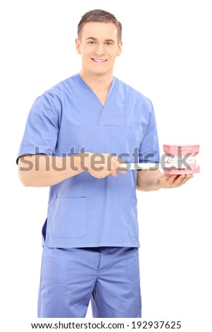 Male dentist holding a toothbrush and a denture isolated on white background