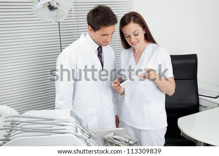 Male dentist with assistant discussing dental report in clinic - stock photo