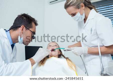 Male dentist with assistant examining girls teeth in the dentists chair - stock photo