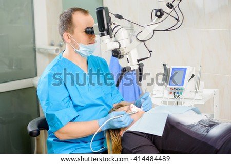 Male dentist working with microscope at modern dentist office. Teeth care and tooth health. Doctor treating root canals through the microscope. Stomatology equipment - stock photo
