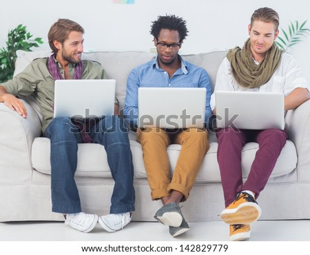 Male designers working together with laptops sit on a sofa - stock photo