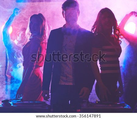 Male dj enjoying party with women behind - stock photo