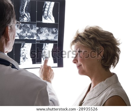 Male doctor and female patient discussing film scans of the patient's back. - stock photo