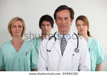 Male doctor and his nursing team - stock photo