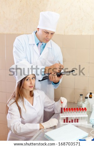 Male doctor and nurse with test tubes makes blood test in medical laboratory
