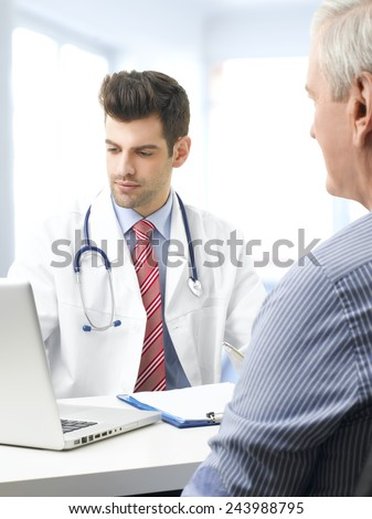 Male doctor and old man analyzing the result of the test on computer while sitting at desk at clinic.  - stock photo