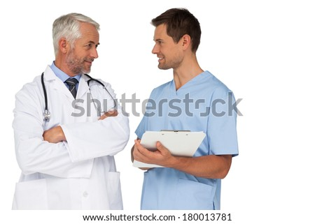 Male doctor and surgeon discussing reports over white background - stock photo