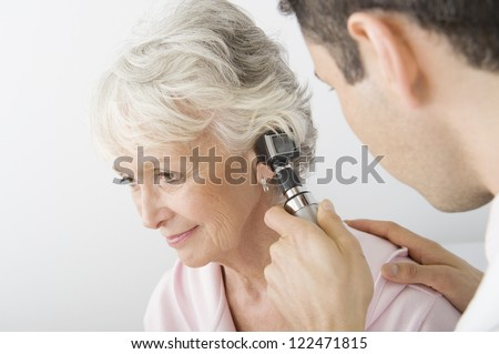 Male doctor checking patient's ear using otoscope - stock photo
