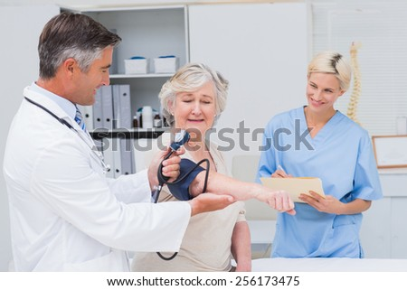 Male doctor checking senior patients blood pressure while nurse noting it in clinic - stock photo