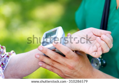 Male doctor checking senior woman blood pressure - stock photo