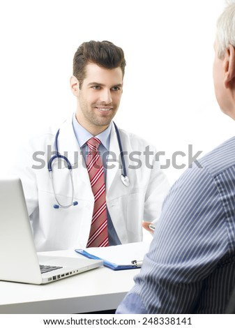 Male doctor consulting his elderly patient while they are sitting in front of computer.  - stock photo