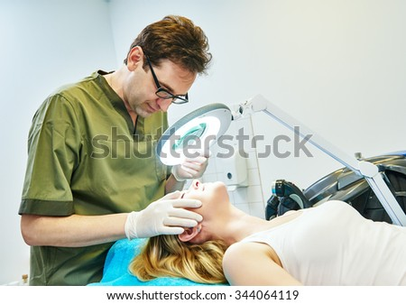 Male doctor cosmetologist examining young woman skin with loupe before the cosmetology procedure - stock photo