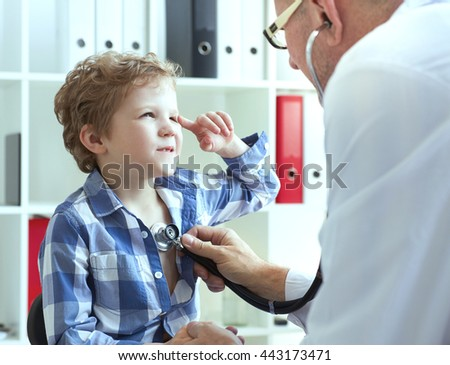 Male doctor examining a child patient by  stethoscope. Health care concept. - stock photo