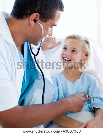 Male doctor examining a child patient in a hospital