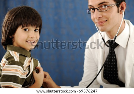 Male doctor examining a child patient in a hospital and kid looking at camera - stock photo