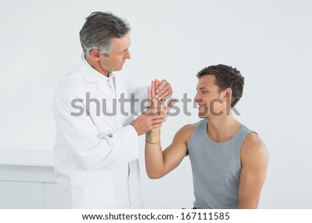 Male doctor examining a patients hand in the medical office - stock photo