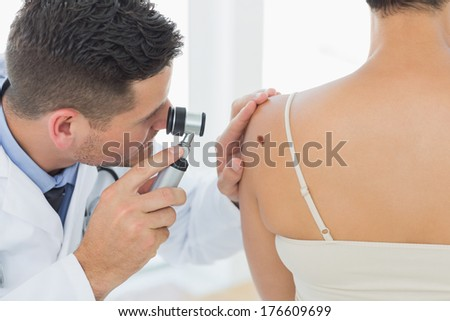 Male doctor examining mole on back of woman in clinic - stock photo