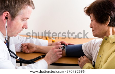 Male doctor examining senior woman with stethoscope for blood pressure at table.  Selective focus on Stethoscope and doctor hand up front.   - stock photo
