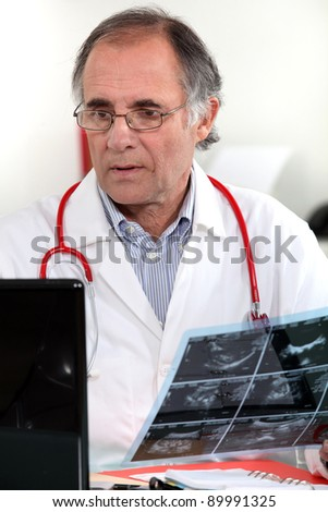 Male doctor examining x-ray - stock photo