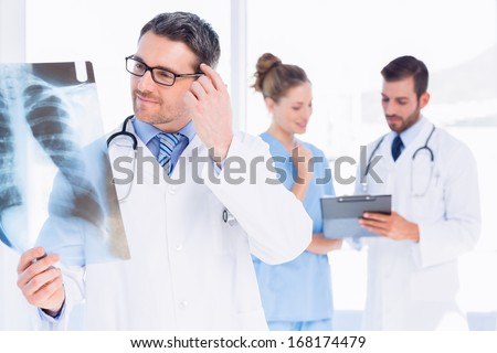Male doctor examining x-ray with colleagues in the background at medical office