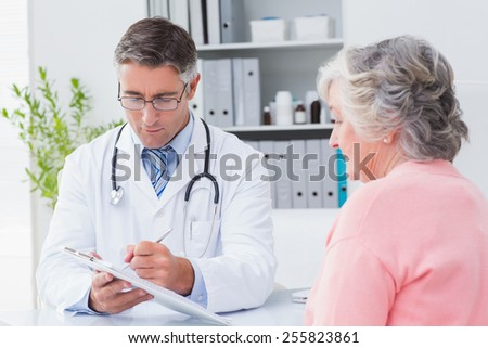 Male doctor explaining prescriptions to senior woman in clinic - stock photo