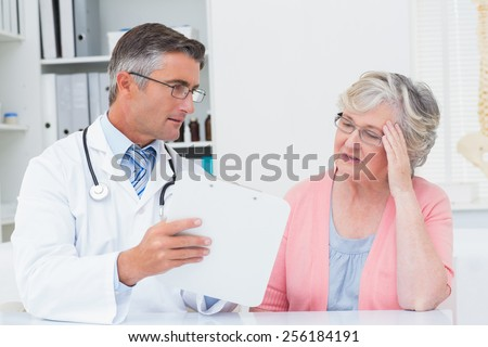 Male doctor explaining prescriptions to tensed senior woman in clinic - stock photo