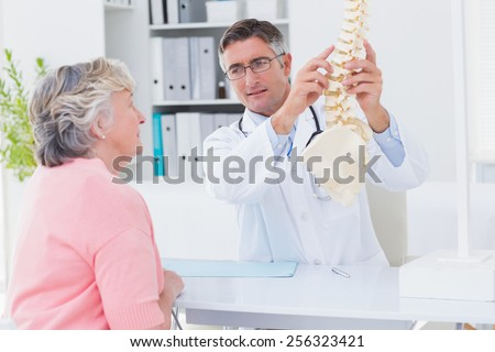 Male doctor explaning anatomical spine to female patient in clinic - stock photo