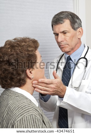 Male doctor feeling female patient's neck for swollen glands. - stock photo
