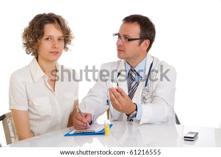 Male doctor giving pills to a patient in a practice - stock photo