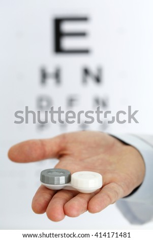 Male doctor hands giving pair of contact lens in case to patient offering choice isolated. Eyesight correction. Ophthalmology, excellent vision or optician shop concept. Laser surgery alternative - stock photo