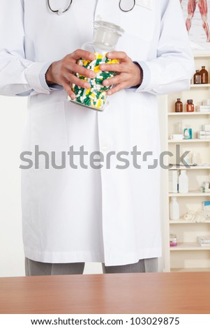 Male doctor holding a bottle with pills.
